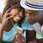 Happy young couple listening to music on the grass
